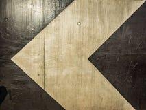 freccia bianca su una parete nera Fotografie Stock