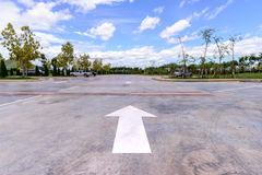 freccia bianca sul parcheggio con il fondo delle automobili Fotografie Stock