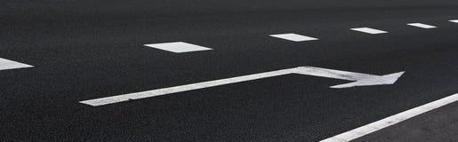 Freccia bianca sull'asfalto immagine stock
