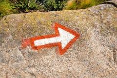 Freccia che segna un percorso di alpinismo su una roccia Immagine Stock