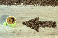 Freccia dai chicchi di caffè con la tazza di caffè sul backgro di legno Fotografia Stock