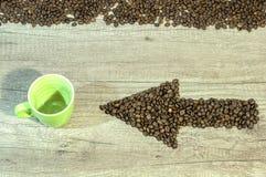 Freccia dai chicchi di caffè con la tazza vuota della bevanda sulla tavola di legno Fotografia Stock Libera da Diritti