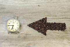 Freccia dai chicchi di caffè con un orologio su fondo di legno Immagini Stock
