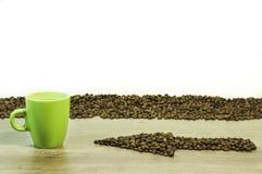 Freccia dai chicchi di caffè con una tazza della bevanda sulla tavola di legno Immagini Stock Libere da Diritti