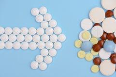 Freccia delle pillole bianche e pila di compresse su un fondo blu Immagine Stock