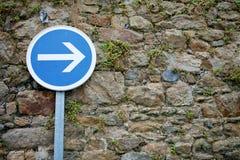Freccia a destra del segnale stradale sui vecchi precedenti della parete di pietra Fotografia Stock