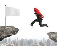 Freccia di trasporto di salto dell'uomo d'affari sul segno diminuire sulla scogliera Fotografia Stock