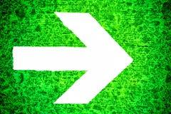 Freccia direzionale bianca che indica verso la destra dipinta su una struttura di legno irregolare grungy verde intenso immagini stock