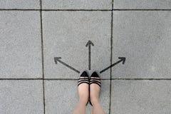 Freccia direzionale e coppie la donna delle scarpe del nero che sta sui precedenti delle mattonelle Immagine Stock Libera da Diritti