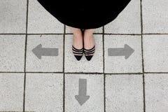 Freccia direzionale e coppie la donna delle scarpe del nero che sta sui precedenti delle mattonelle Fotografia Stock
