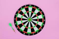 Freccia e bersaglio verdi del dardo, su fondo pastello rosa Disposizione piana Copi lo spazio immagine stock libera da diritti