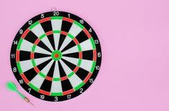 Freccia e bersaglio verdi del dardo, su fondo pastello rosa Disposizione piana Copi lo spazio immagini stock