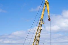 Freccia gialla della gru del porto contro il cielo blu e le nuvole Fotografia Stock Libera da Diritti
