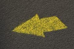 Freccia gialla dipinta sulla strada asfaltata che indica direzione Fotografia Stock