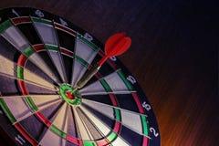 Freccia rossa dei dardi sul bersaglio concentrare dell'obiettivo sul pavimento di legno fotografia stock