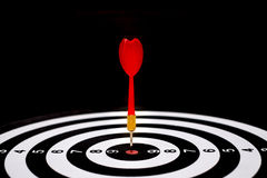 Freccia rossa del dardo che colpisce nel centro dell'obiettivo del bersaglio Fotografia Stock