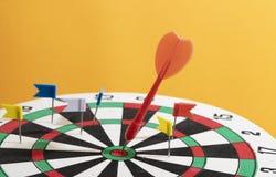 Freccia rossa del dardo nell'obiettivo su fondo arancio, scopo di affari immagini stock