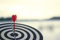Freccia rossa sparata del dardo nel centro del bersaglio Concetto per mirare al successo ed al vincitore immagine stock