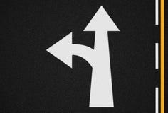 Freccia su struttura della strada asfaltata e sulle linee di traffico Immagini Stock