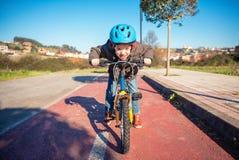 Frecher Junge mit aufsässiger Geste über seinem Fahrrad Lizenzfreie Stockbilder