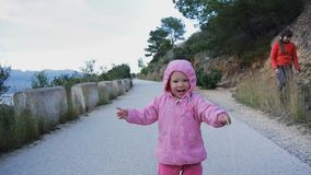 Freches kaukasisches Baby in der Haube mit Kraut strow lachenden Läufen auf der Gebirgsstraße, die versucht, die Kamera zu jagen  stock video footage