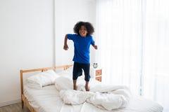 Freches Kind des glücklichen Afroamerikaners, das auf das Bett mit Glück springt stockfotografie
