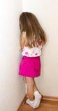 Freches kleines Mädchen steht in der Ecke Stockbilder