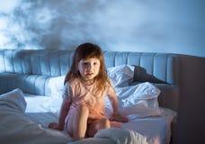 Freches Mädchen, das auf dem Bett in der Nacht sitzt Lizenzfreies Stockfoto