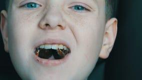 Freckled blonde jongenstiener die chocoladesuikergoed dicht omhoog eten stock footage