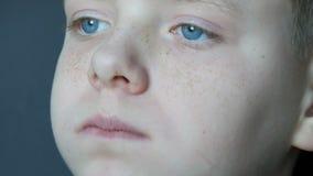 Freckled blonde jongenstiener die met zijn blauwe ogen chocoladesuikergoed eten bekijkt dicht omhoog stock footage