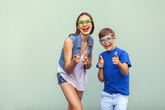 The freckled brother and sister in casual t shirts wearing trendy glasses and posing over light green background together. Stock Photos