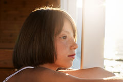 Freckled child with bobbed hairdo, looking into distanse, admiring beautiful sea landscapes, dreaming about something. Little girl Stock Image