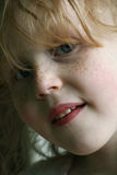 Freckled face of girl. A closeup portrait of the face of a cute little girl with red hair and freckles Royalty Free Stock Images