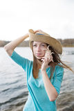 Freckled girl in hat listening to shell and standing on lake Royalty Free Stock Image