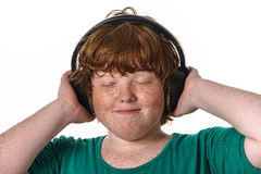 Freckled red-hair boy listening music. Stock Photo