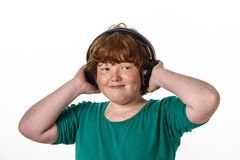 Freckled red-hair boy listening music. Royalty Free Stock Image