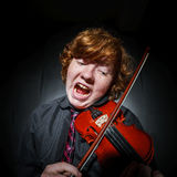 Freckled red-hair boy playing violin Stock Image