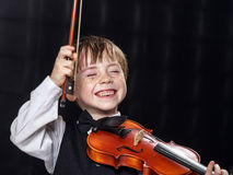 Freckled red-hair boy playing violin. Royalty Free Stock Image