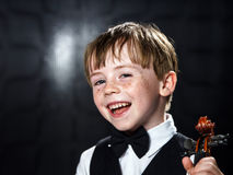 Freckled red-hair boy playing violin. Royalty Free Stock Photos