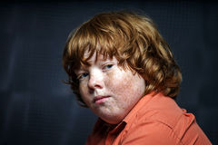 Freckled red-hair boy posing on dark background. Stock Photography