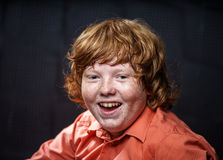 Freckled red-hair boy posing on dark background. Royalty Free Stock Images