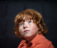 Freckled red-hair boy posing on dark background. Stock Images