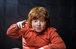 Freckled red-hair boy posing on dark background. Royalty Free Stock Photo