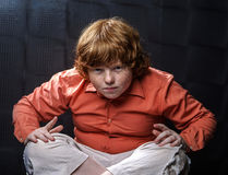 Freckled red-hair boy posing on dark background. Emotions Royalty Free Stock Photography