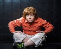 Freckled red-hair boy posing on dark background. Emotions Stock Photography