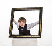 Freckled red-hair little boy with big picture frame. Stock Image