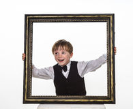 Freckled red-hair little boy with big picture frame. Stock Photos