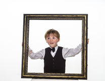 Freckled red-hair little boy with big picture frame. Royalty Free Stock Photo