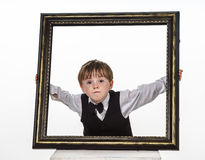 Freckled red-hair little boy with big picture frame. Stock Images