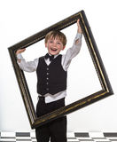 Freckled red-hair little boy with big picture frame. Royalty Free Stock Image